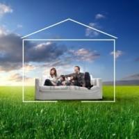 6624832-sorridente-famiglia-seduta-su-un-divano-circondato-dalla-forma-di-una-casa-su-un-prato-verde